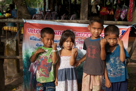 -	Children in Lao hold up their marked pinky fingers to show they have been immunized in Lao's succesful 2011 measles-rubella campaign